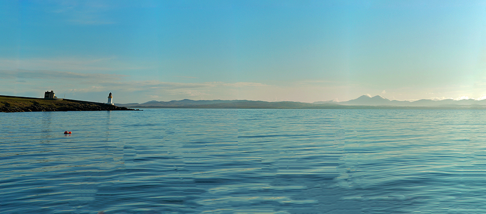 Panoramic picture of a view over a sea loch, a lighthouse on the left, mountains in the haze in the distance