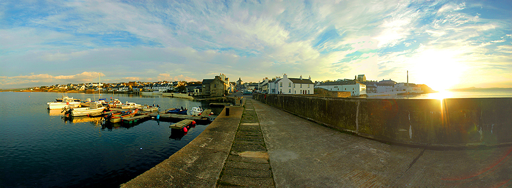 Panoramic picture of a coastal village from the pier in the mild October afternoon sunshine during an approaching sunset
