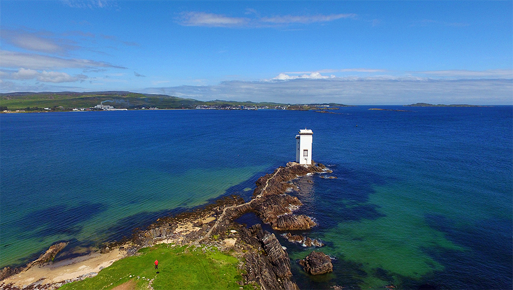 Picture of a drone view of a square lighthouse with a coastal village in the distance in the background