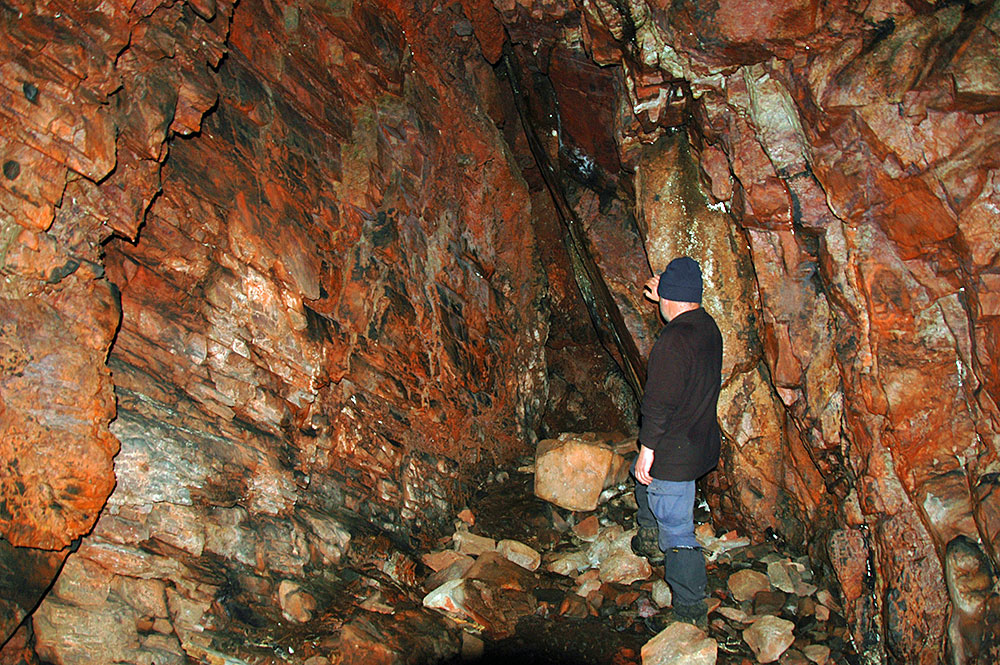 Picture of a man looking at rocks in a cave