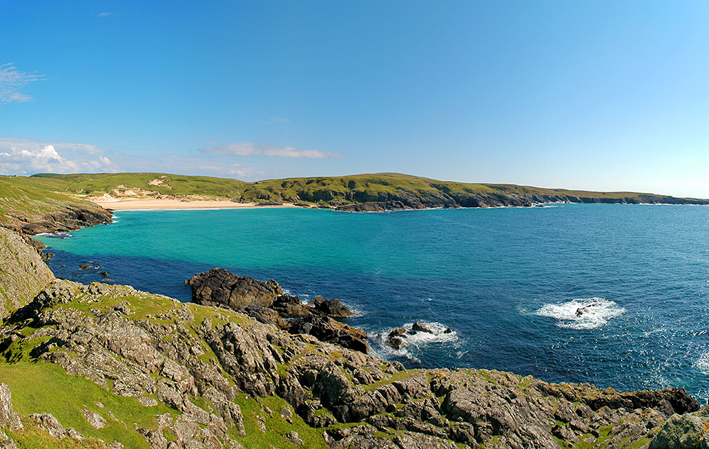 Panoramic picture of a bay with a beach with cliffs on both sides