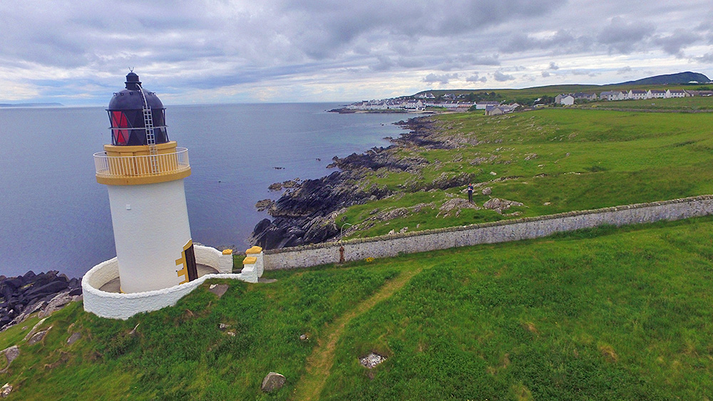Aerial picture of a small lighthouse on a rocky shore with a small coastal village in the background