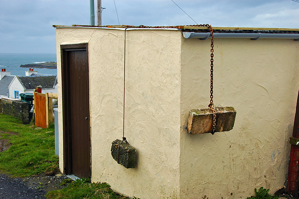 Picture of a shed in a coastal village, its roof weighed down with large bricks on chains and ropes