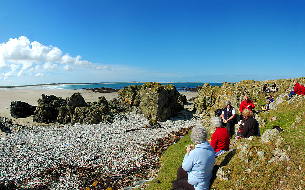 Panoramic picture of a group of walkers enjoying a lunch with a view at the end of a bay with a wide beach