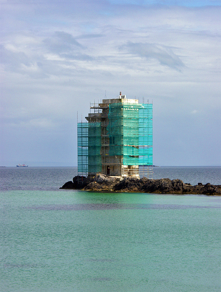 Picture of a square lighthouse with scaffolding around it