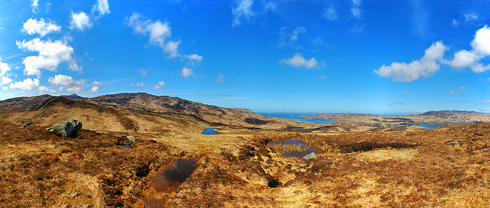 Picture of a remote hilly landscape with several small lochs and a larger sea loch in the distance