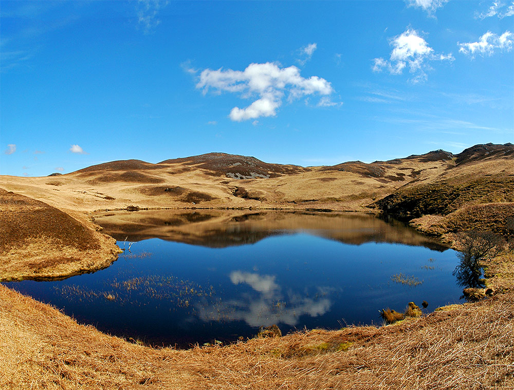 Panoramic picture of clouds and hills reflecting in a lochan