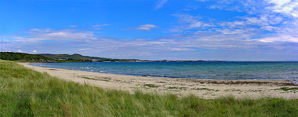 Panoramic picture of a beach on a bay, a village in the distance on the other side of the bay