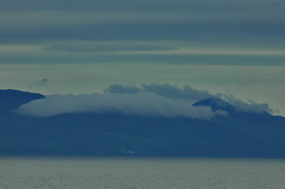 Picture of low clouds over coastal hills above a lighthouse