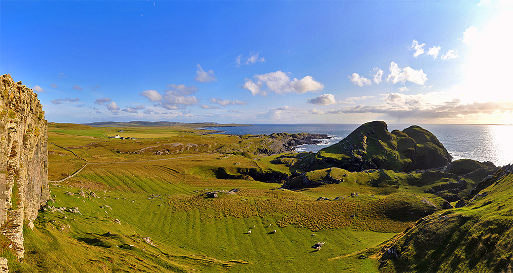 Panoramic picture of a varied coastal landscape with fields and cliffs