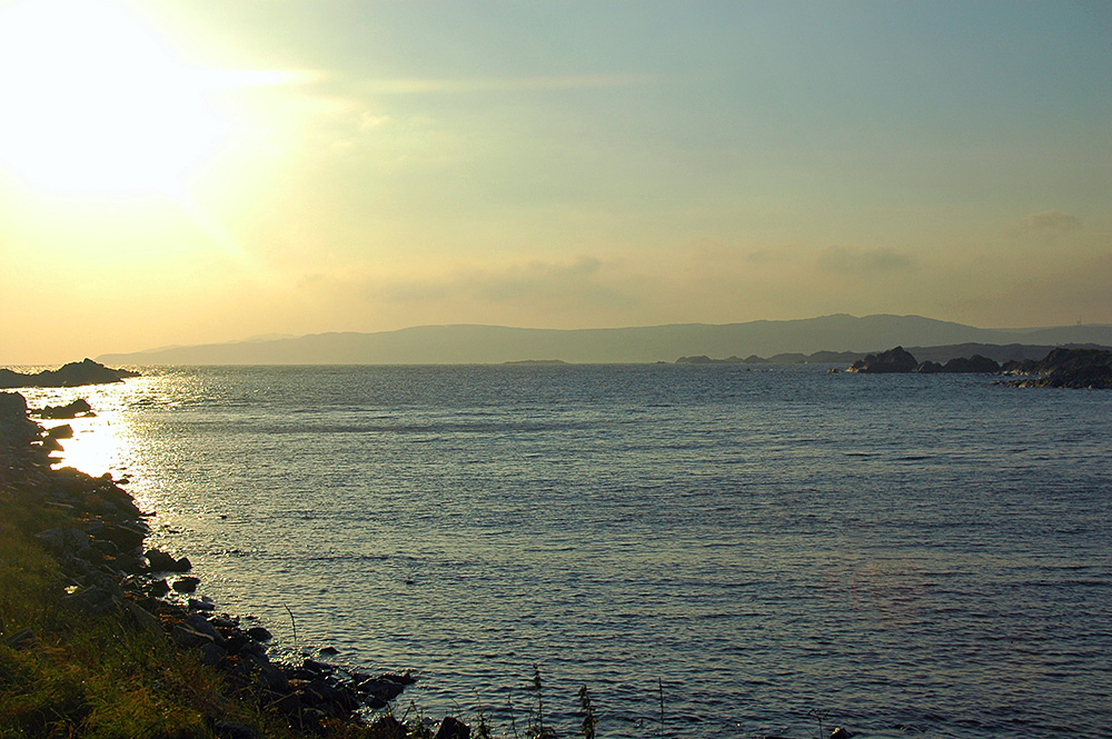 Picture of a view over a small sea loch with a high coastline in the distance