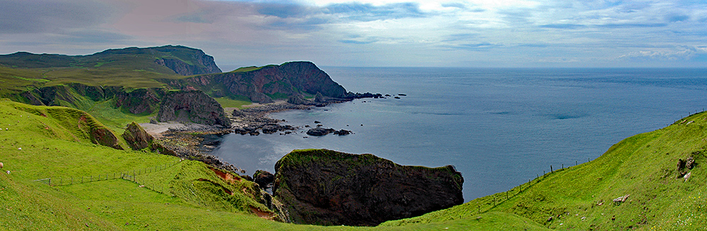 Panoramic picture of a coastal landscape with steep cliffs below a grass covered top
