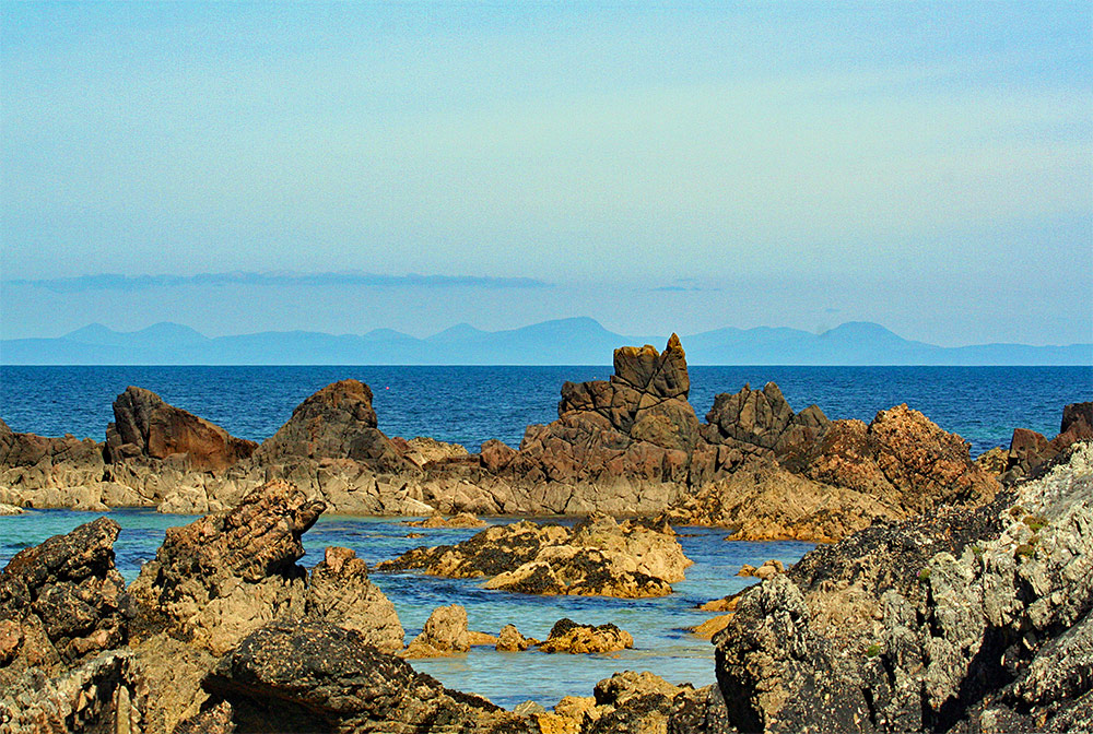 Picture of a rocky shallow coastline looking out to sea with another island in the distance
