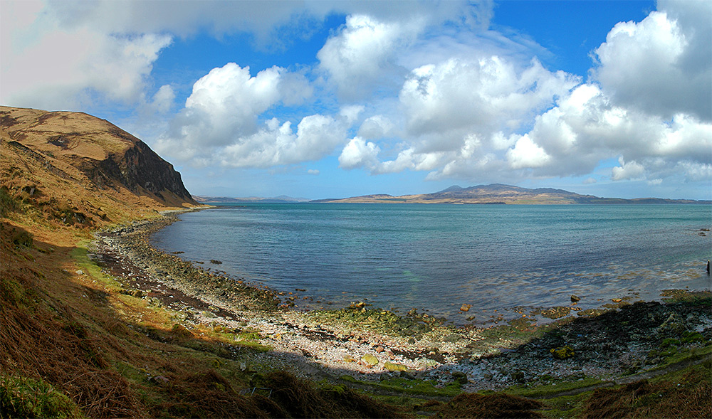 Panoramic picture of a sound between two islands from a shore with steep cliffs above
