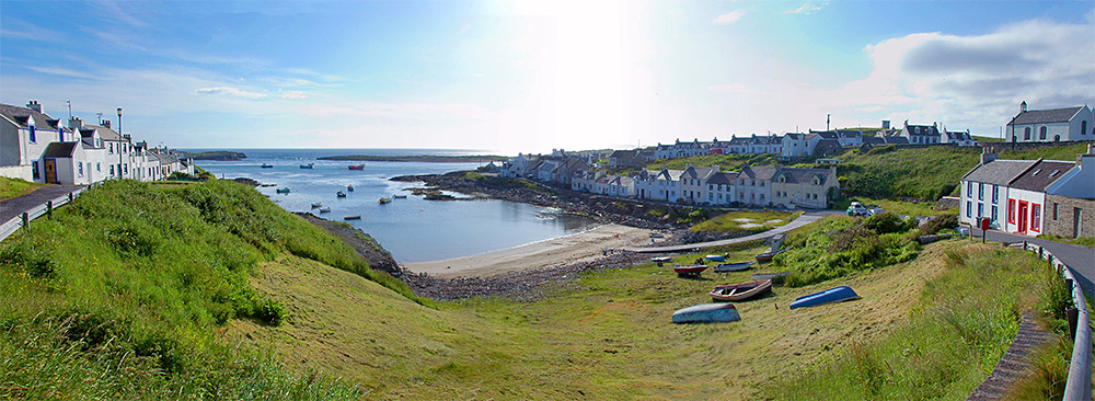 Panoramic picture of a coastal village around a small inlet on a sunny June day