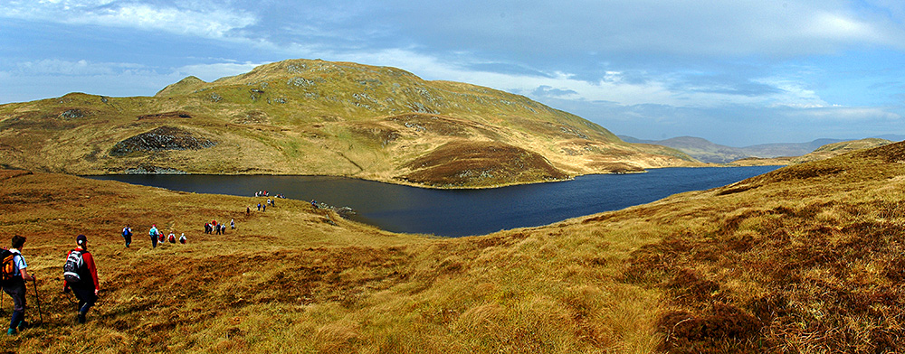 Panoramic picture of a group of walkers arriving a loch in the hills