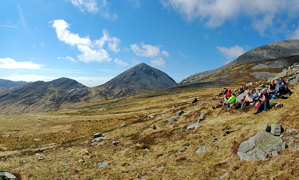 Panoramic picture of a group of walkers enjoying a rest break with a view half way up a mountain