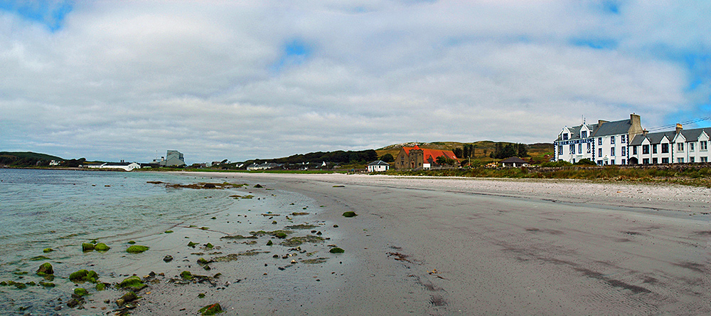 Panoramic picture of a beach, a distillery and modern maltings in the distance, a hotel called White Hart at the start of the beach