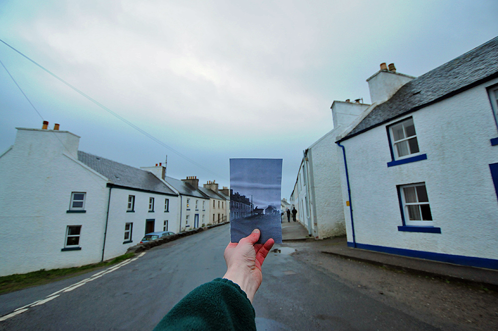 Picture of a village main street with an old picture of the street held in place