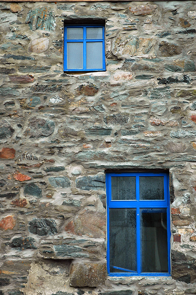 Picture of two blue painted windows in a stone house wall