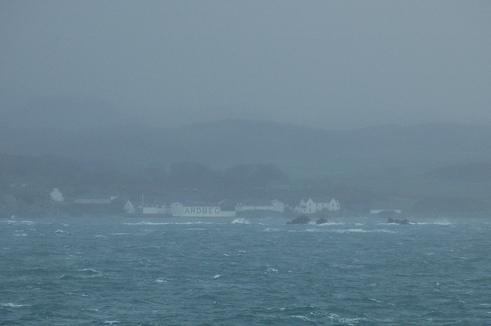 Picture of Ardbeg distillery on a blustery and rainy day, seen from a passing ferry