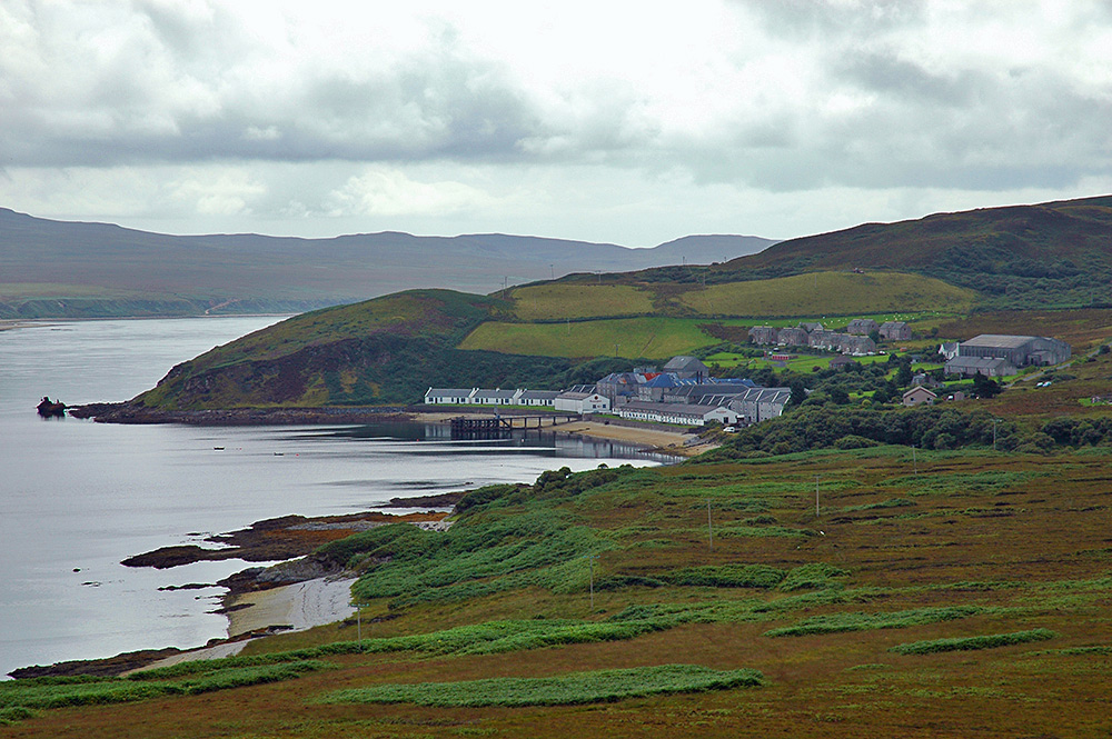 Picture of a coastal distillery (Bunnahabhain on Islay) with an old wreck just down the shore