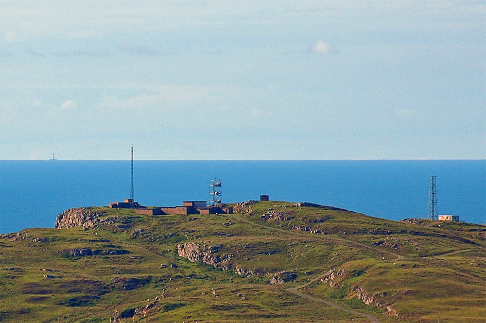 Picture of an old radar station on the top of a coastal hill with a lighthouse on the horizon across the sea