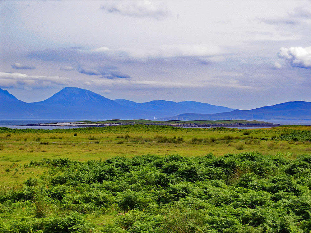 Picture of a view from an island to two other islands, a lighthouse just visible on one of them