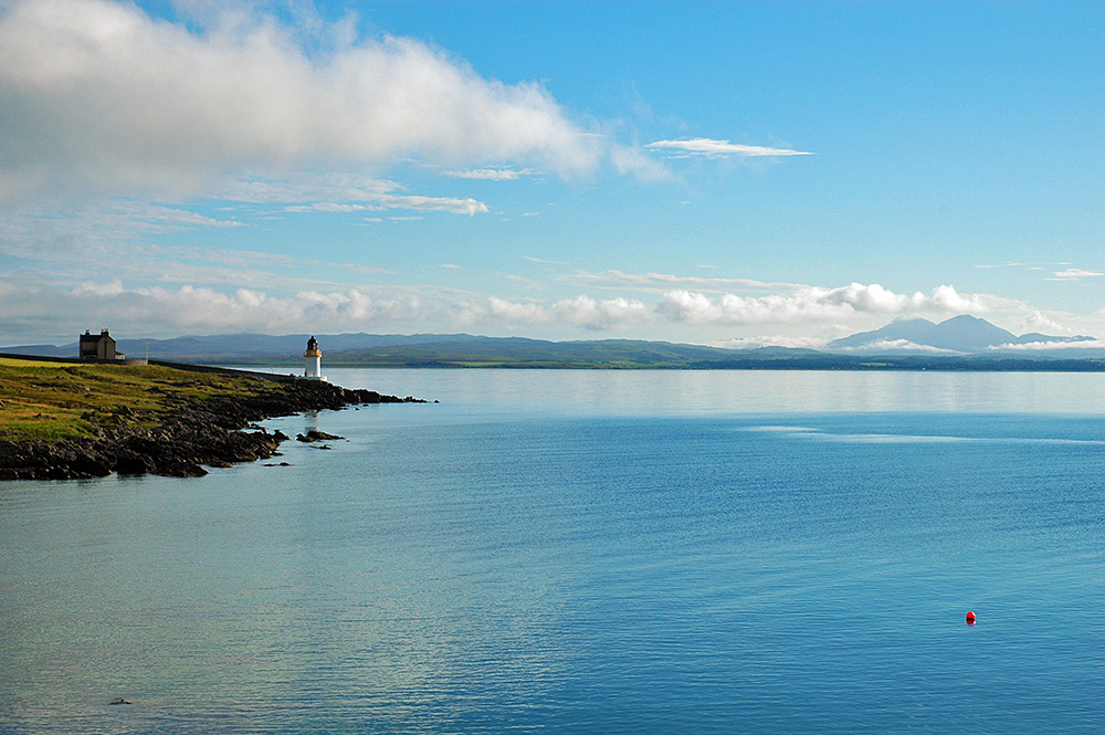 Picture of a lighthouse at the sea loch, three high mountains in the distance
