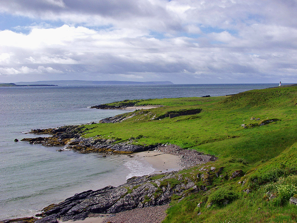 Picture of a stretch of coast along a sea loch, small beaches in the foreground and a small lighthouse in the distance