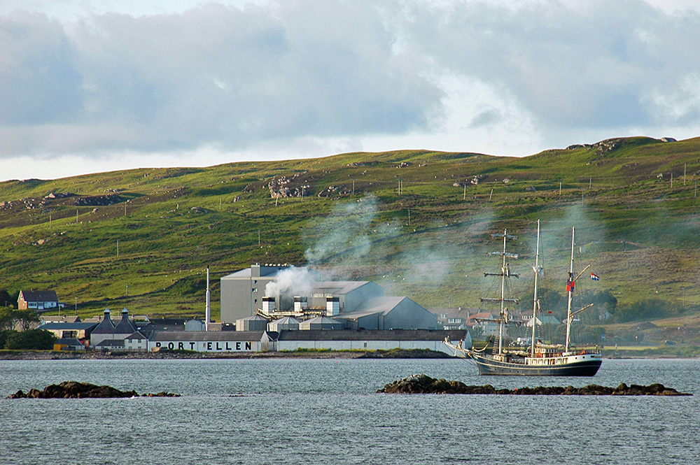 Picture of an old distillery with modern maltings with a tall ship moored offshore