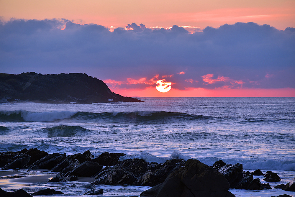 Picture of a colourful sunset at a bay with rocks on a beach and rocky cliffs
