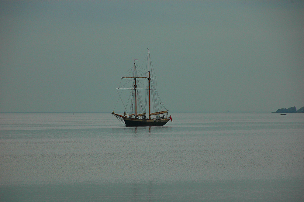 Picture of a sailing ship on an overcast day in a bay