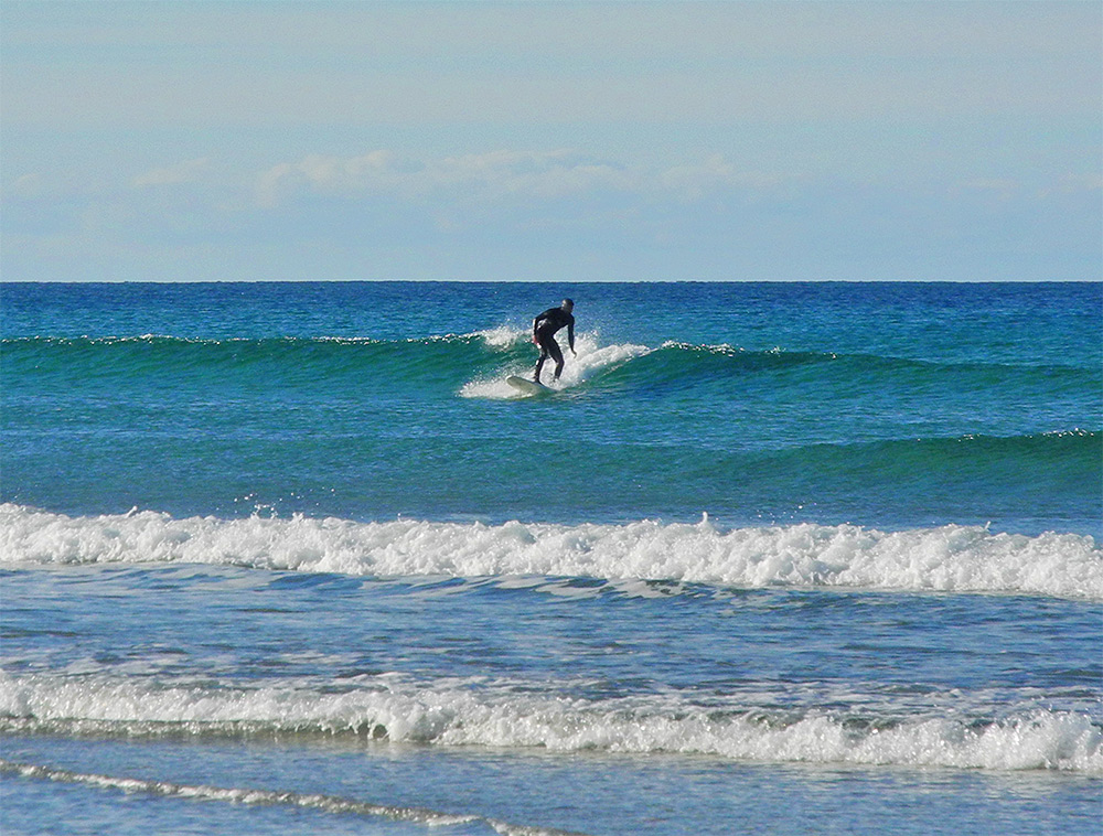 Picture of a surfer riding a small wave