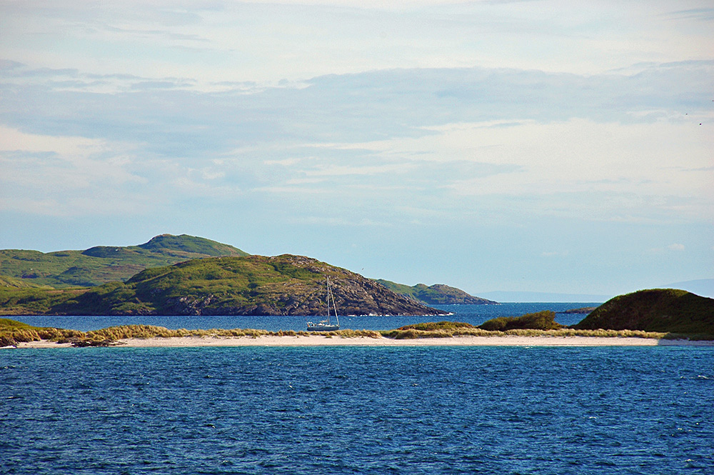 Picture of a yacht anchored behind a tombolo with twin beaches, seen from a passing ferry