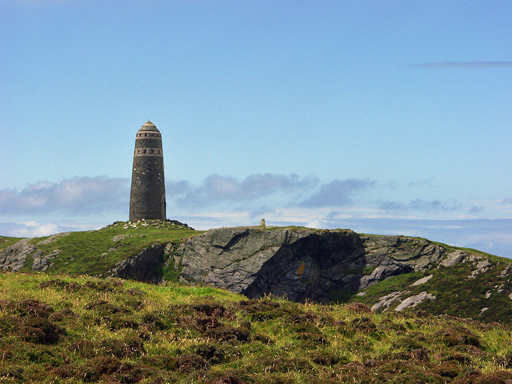 Picture of a monument on the top of steep cliffs on a sunny day