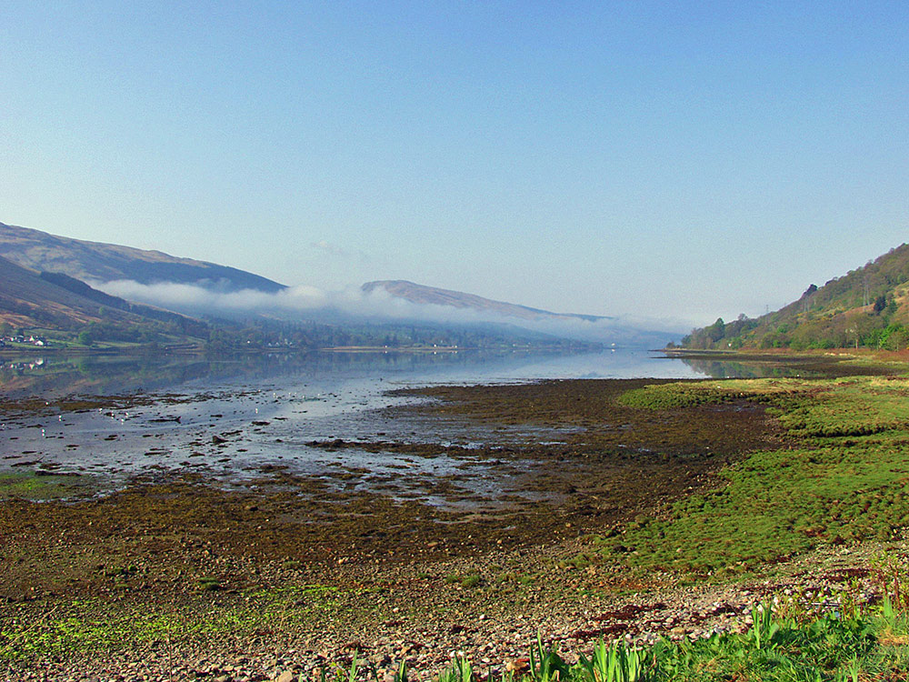 Picture of a sea loch on an April morning with low clouds wafting over the loch
