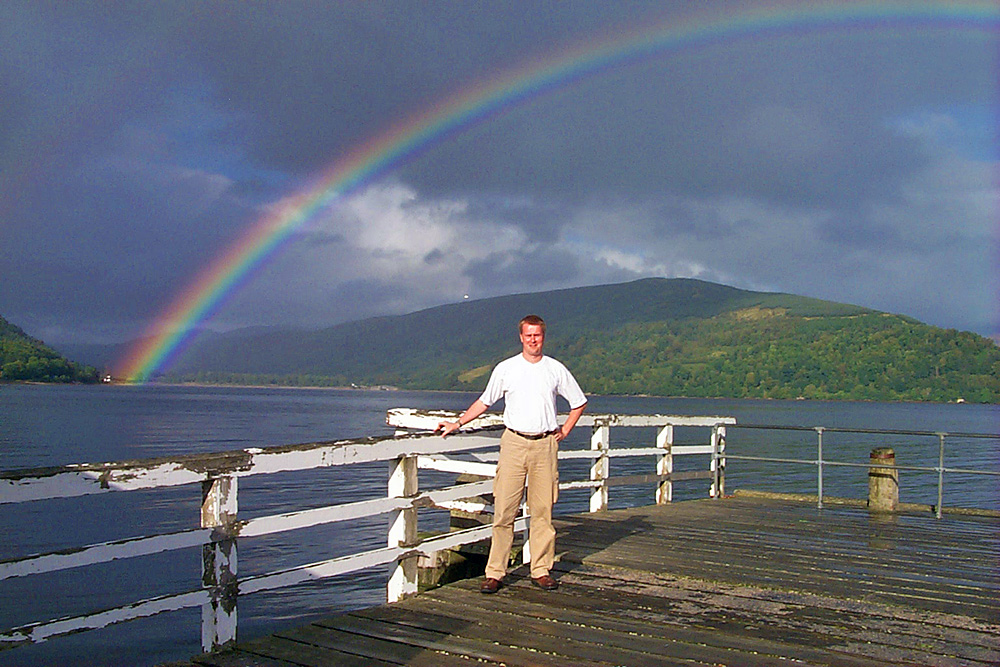 Picture of a man standing on a pier under a rainbow