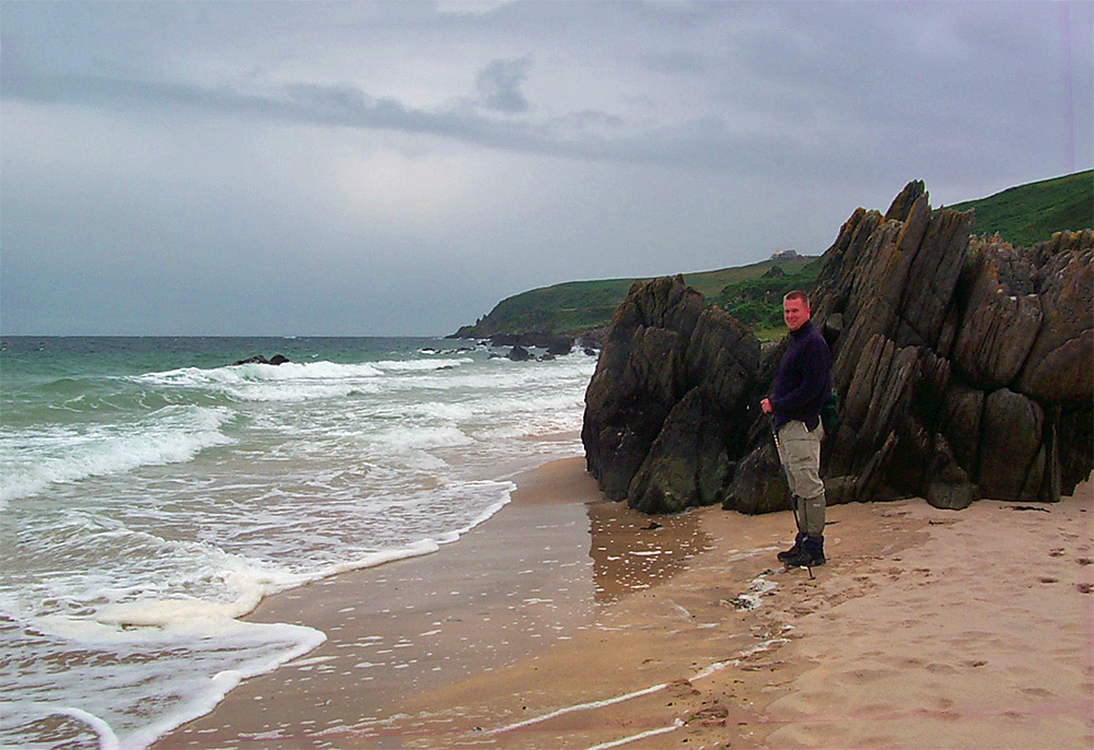 Picture of a man standing in front of rocks on a beach on a cloudy day