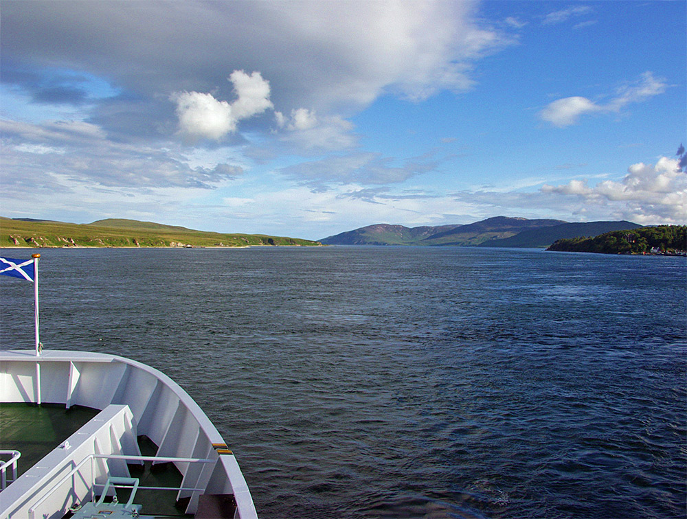 Picture of a ferry travelling through a sound between two islands, a small village/port on the right
