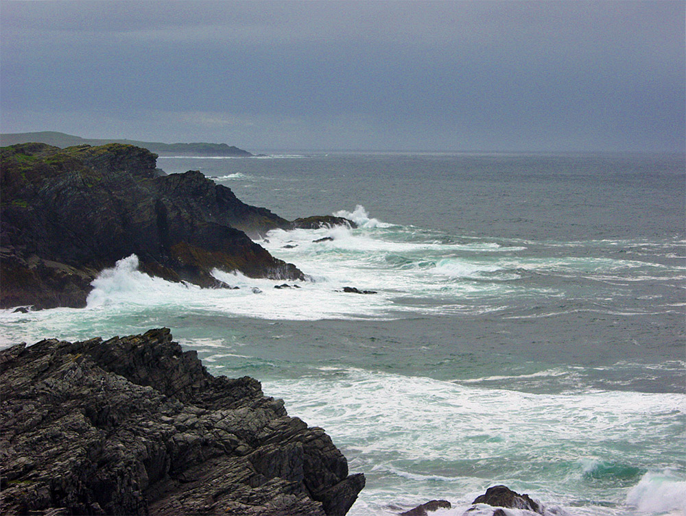 Picture of cliffs and waves under a dark, grey, cloudy sky