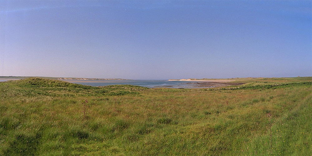 Panoramic picture of the mouth of a sea loch seen from the shore, dunes on both sides of the loch