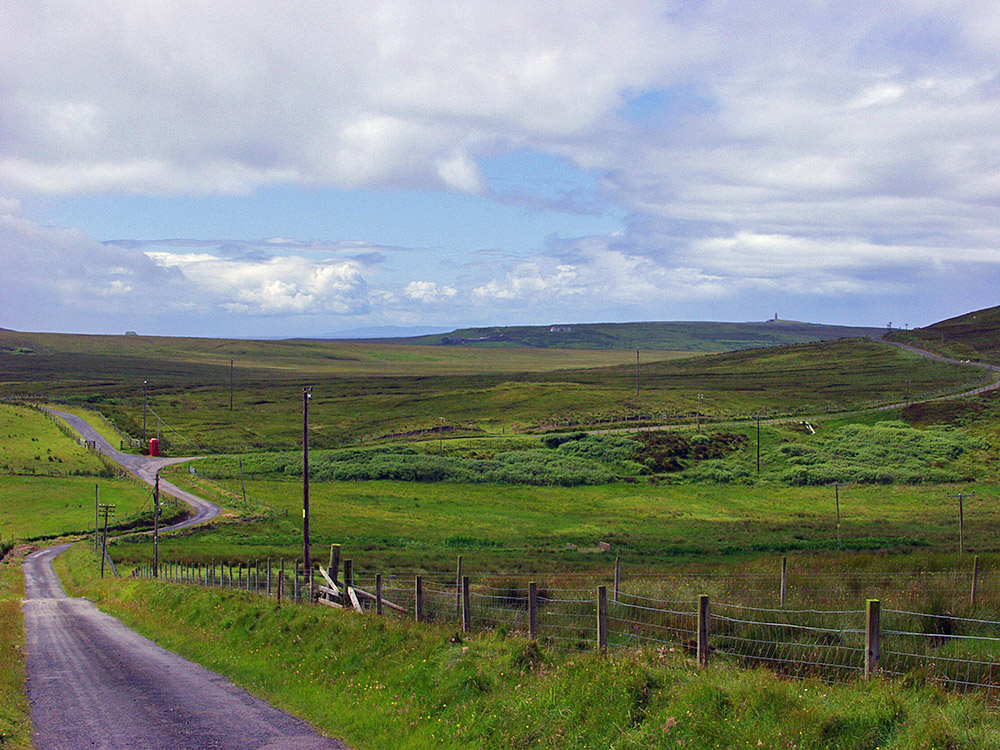 Picture of a wide landscape with a single track road, a red phone box at the road, a monument in the distance