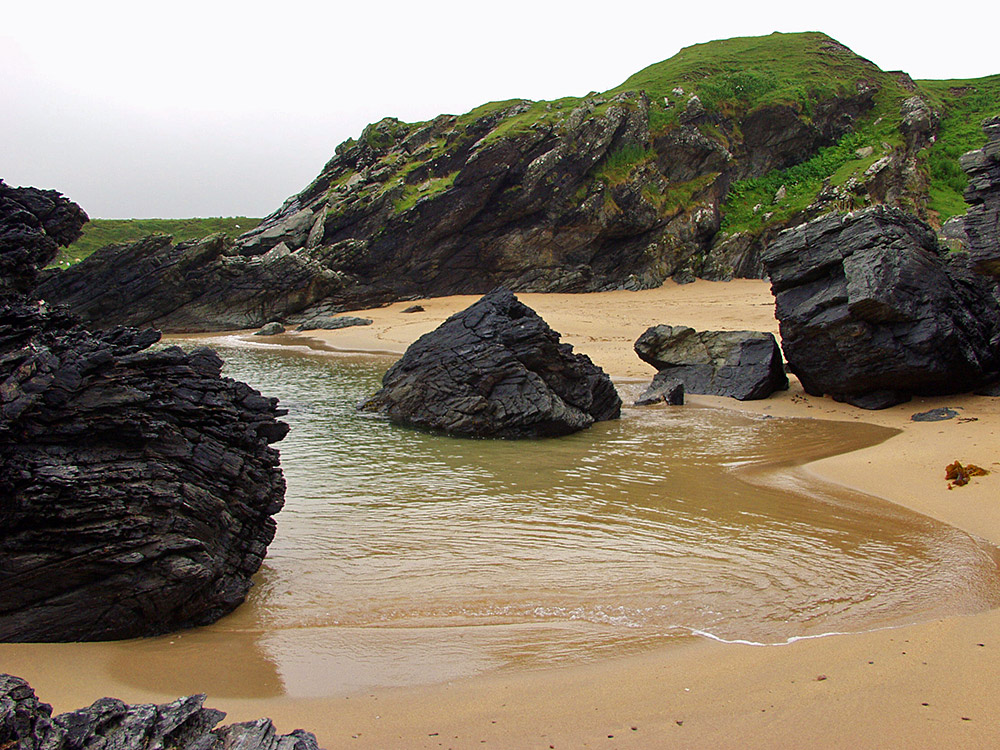 Picture of a beach with various rocks embedded and behind, water lapping on the beach