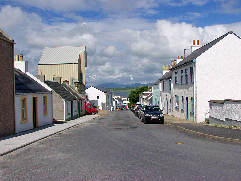Picture of a view down a village street, a loch visible in the distance