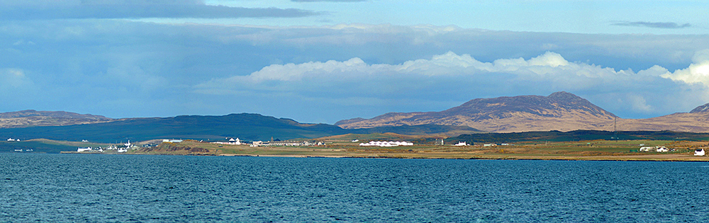 Panoramic picture of a coastal village seen across a wide sea loch