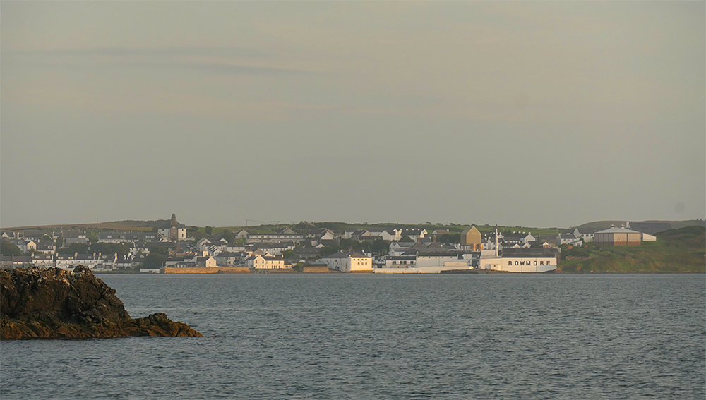 Picture of Bowmore village with the distillery seen across Loch Indaal, rocks in the foreground