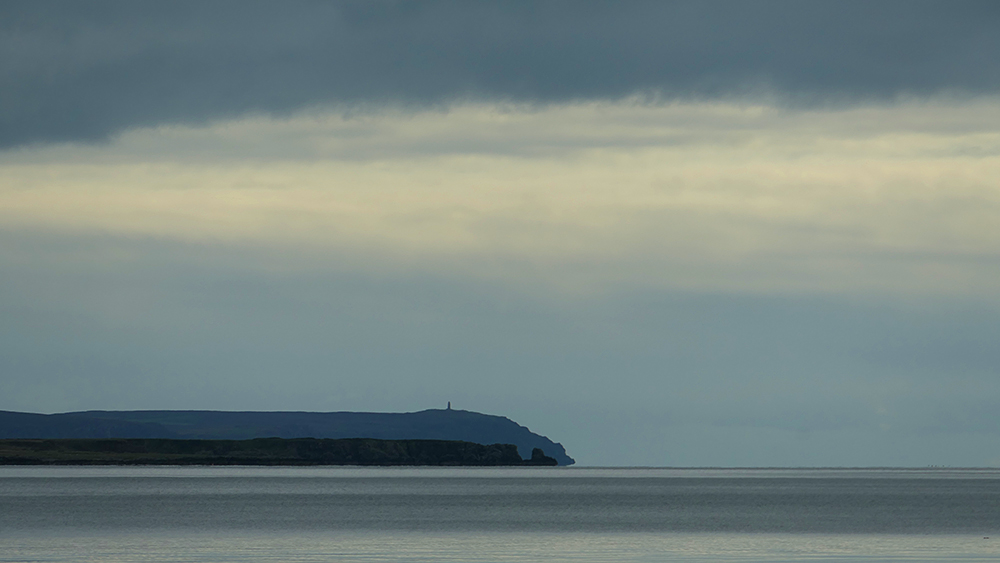 Picture of two coastal points, one with a monument on the top, on a cloudy day