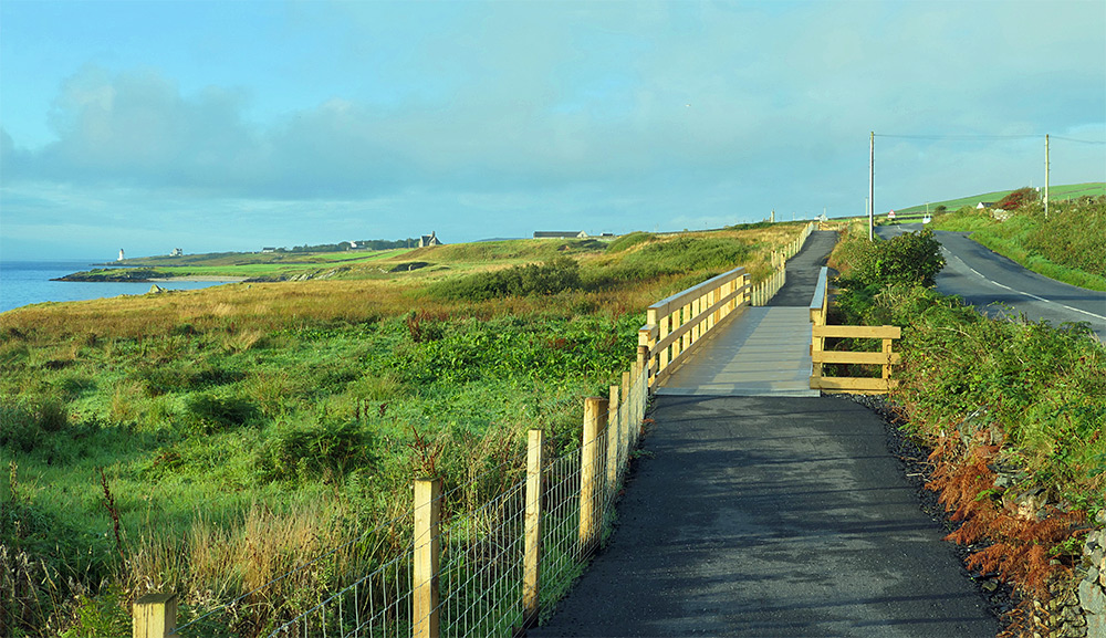 Picture of a new footpath with a wooden bridge parallel to a road along a sea loch
