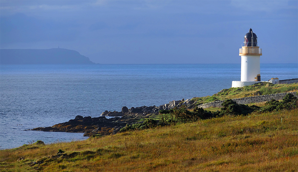 Picture of a lighthouse on the shore of a sea loch, the mull of a peninsula visible in the haze in the distance